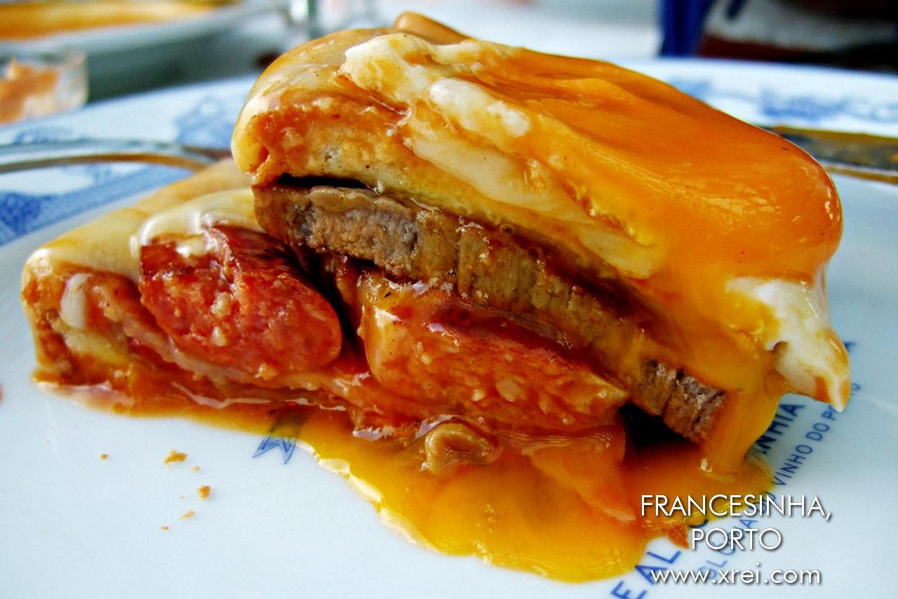"""Francesinha es una especialidad de Oporto que consiste principalmente en salchichas, salchichas frescas, jamón, embutidos y bistec de ternera, cubierto con salsa de queso y tomate, cerveza y piri-piri, variación del sándwich francés croque-monsieur. """""""