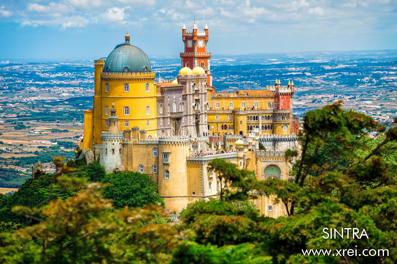 Pena Palace is the Portuguese ex-libris of Romanticism. It is a palace located at the top of the Serra de Sintra with an architecture mix of various styles, inspired by the Castle of Louis II of Bavaria. The colors of the palace make the architecture and the environment extremely fascinating. This image of the Pena Palace was taken from the highest point in Sintra, the Cruz Alta viewpoint.