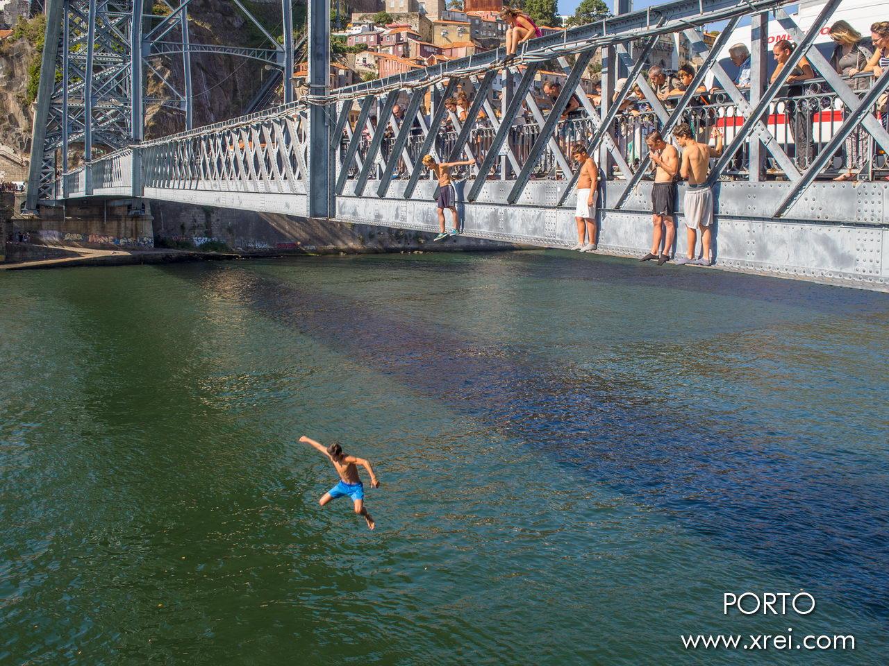 Adolescentes saltando del puente Dom Luís I al río, bajo la observación de los turistas