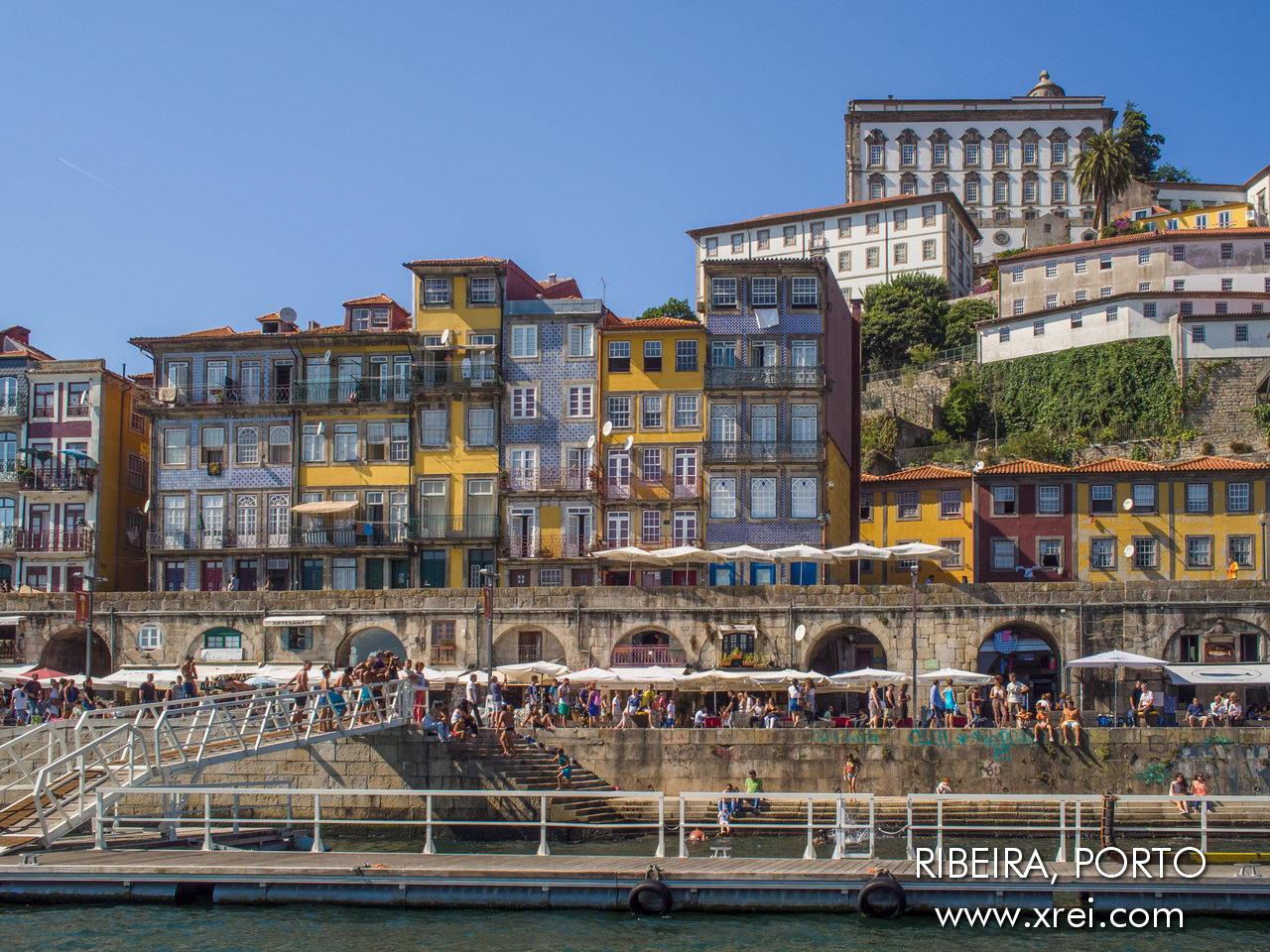 En esta foto podemos ver el histórico paseo costero de Ribeira do Porto, con la muralla, las casas recuperadas de la ladera y el Paço Episcopal do Porto en lo alto de la colina.