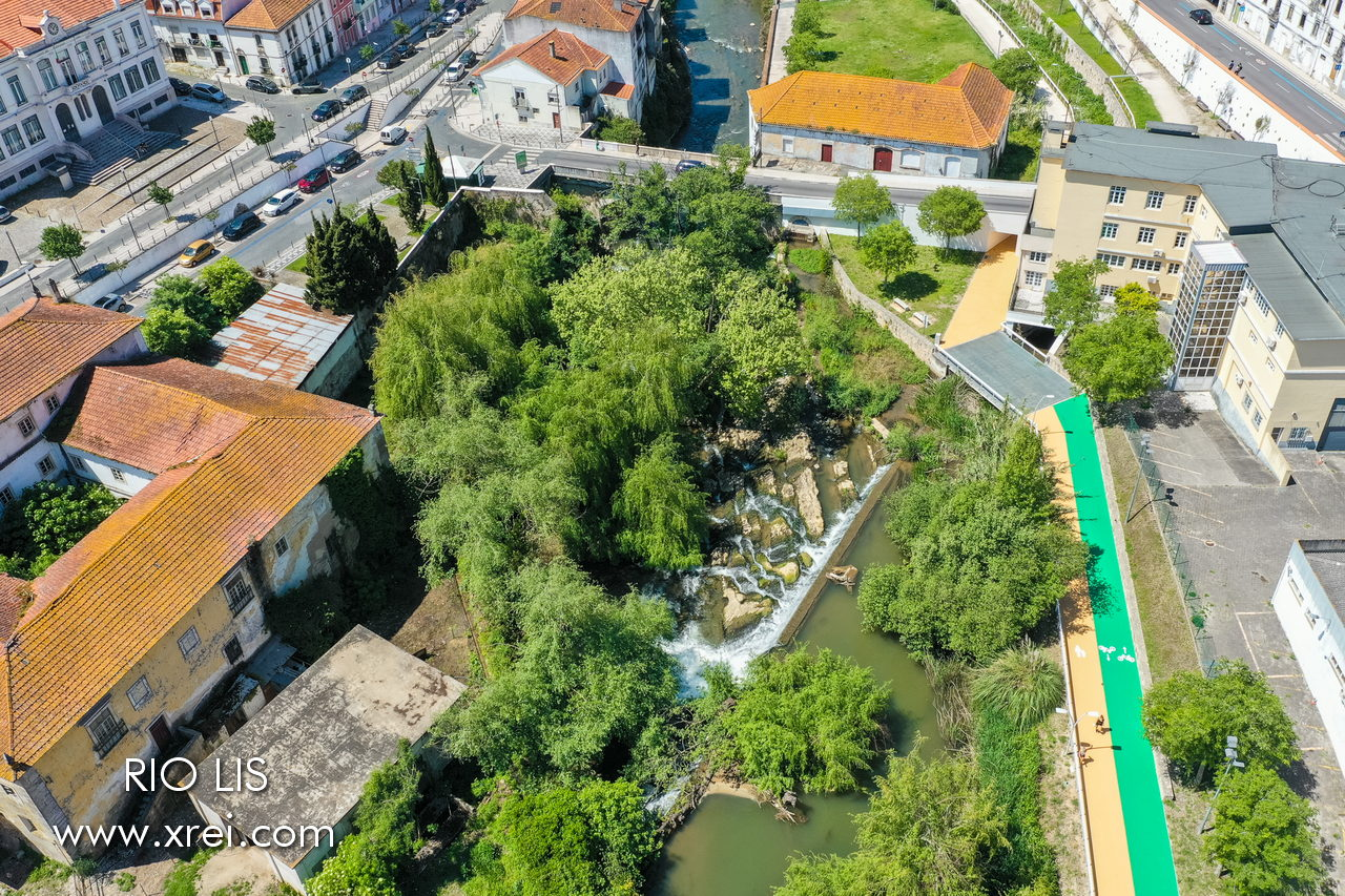 Lis River area in Leiria, with the river passing through vegetation, natural stone waterfalls, and spaces for sport and walking. The atmosphere in this place is fantastic, with the sound of the river water, and the surrounding trees.